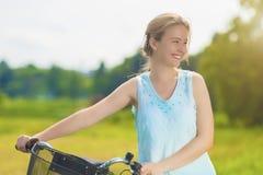 Glückliche schöne blonde Frau, die gute Zeit mit Fahrrad Outdoo hat Stockfotos