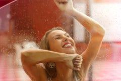 Glückliche schöne blonde Frau, die unter Regen im Herbst lacht Stockbild