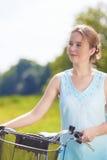 Glückliche schöne blonde Frau mit Fahrrad draußen Stockfotografie