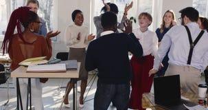 Glückliche schöne blonde Geschäftsfrau in der Abendtoilette, die tanzt, um Erfolg mit Kollegen im modernen Büro zu feiern stock video footage