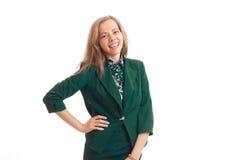 Glückliche schöne Blondine in einer modischen Kleidung wirft im Studio auf und hält eine Hand auf der Seite Lizenzfreies Stockfoto