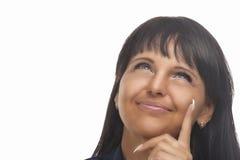 Glückliche schöne Brunette-Frau, die oben schaut. Horizontales Bild Stockfotografie