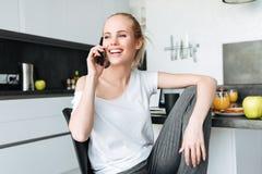 Glückliche schöne Dame, die beiseite bei der Unterhaltung am Telefon schaut Lizenzfreie Stockfotografie