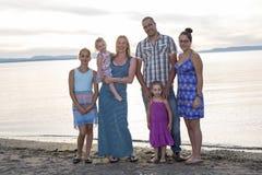 Glückliche schöne Familie, die bei Strandsonnenuntergang steht stockfotografie