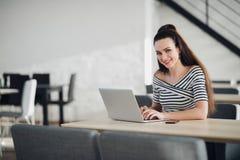 Glückliche schöne freiberuflich tätige berufstätige Frau, die in einem Café mit modernem Innen sitzt und etwas in ihrem Laptop sc stockfotografie