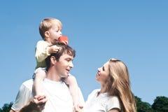 Glückliche schöne junge Familie, die draußen aufwirft. Stockfotos