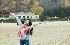 Glückliche schöne junge Frau auf dem kalten Strand Stockfoto