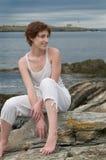 Glückliche schöne junge Frau auf einem felsigen Strand Lizenzfreies Stockfoto