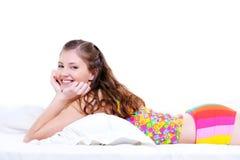 Glückliche schöne junge Frau, die im Bett liegt Stockbild