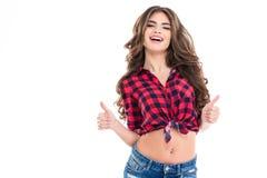 Glückliche schöne junge Frau, die sich Daumen mit beiden Händen zeigt stockbilder