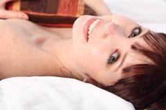Glückliche schöne junge Frau im reizenden Lächeln des Betts Stockfoto