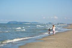 Glückliche schöne junge Mutter und Kind, die weit weg entlang den Seestrand geht Lizenzfreies Stockfoto