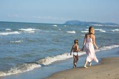 Glückliche schöne junge Mutter und Kind gehen weit weg entlang das Meer Stockfotos