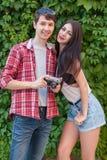 Glückliche schöne junge Paare nahe grüner Wand mit Kamera Betrachten der Kamera Lizenzfreies Stockfoto
