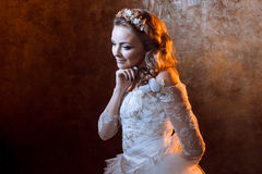 Glückliche schöne Mädchenbraut im luxuriösen Hochzeitskleid, Porträt in den goldenen Tönen, Effekte des grellen Glanzes Lizenzfreies Stockfoto