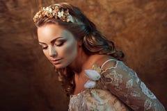 Glückliche schöne Mädchenbraut im luxuriösen Hochzeitskleid, Porträt in den goldenen Tönen, Effekte des grellen Glanzes Stockfotos