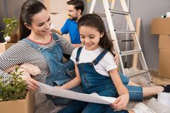 Glückliche schöne Mutter mit kleiner Tochter betrachtet Plan für das Vereinbaren von Räumen im Haus lizenzfreies stockbild