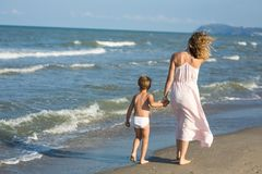 Glückliche schöne Mutter und Kind gehen weit weg entlang den Seestrand, Windschlag Stockbilder