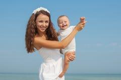 Glückliche schöne Mutter und Sohn, die Strandzeit genießt Stockbilder