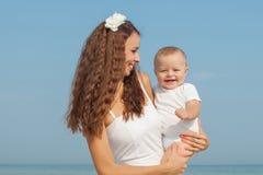 Glückliche schöne Mutter und Sohn, die Strandzeit genießt Stockfotos