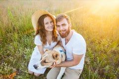 Glückliche schöne Paare mit ihrem Alabai-Hund in der Natur mit Sonnenuntergang stockfotos