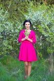 Glückliche schöne träumerische Frau im rosa Kleid im Frühjahr gehend che Stockbilder