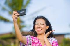 Glückliche schöne und herrliche asiatische Chinesin im Zauberkleid, das Selbstporträt selfie Foto mit Handy an den Feiertagen mac Lizenzfreies Stockfoto