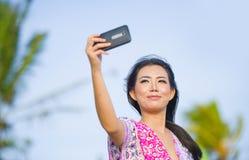 Glückliche schöne und herrliche asiatische Chinesin im Zauberkleid, das Selbstporträt selfie Foto mit Handy an den Feiertagen mac Stockfoto