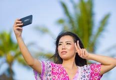 Glückliche schöne und herrliche asiatische Chinesin im Zauberkleid, das Selbstporträt selfie Foto mit Handy an den Feiertagen mac Stockfotografie