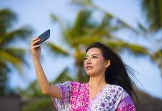 Glückliche schöne und herrliche asiatische Chinesin im Zauberkleid, das Selbstporträt selfie Foto mit Handy an den Feiertagen mac Lizenzfreie Stockfotografie