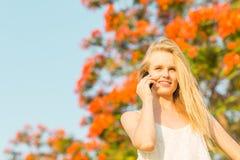 Glückliche Schönheit, die auf einem Mobiltelefon im Park spricht stockfotografie