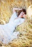 Glückliche schlafende Frau auf dem Weizengebiet Lizenzfreies Stockfoto