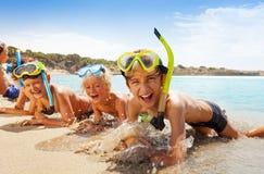 Glückliche schreiende Jungen in der Unterwasseratemgerätmaske auf dem Strand lizenzfreie stockbilder