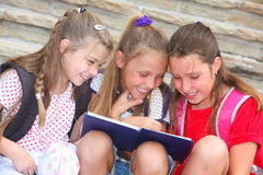 Glückliche Schulmädchen, die ein Buch lesen lizenzfreies stockbild