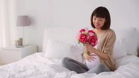 Glückliche schwangere asiatische Frau mit Blumen im Bett stock video footage