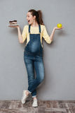 Glückliche schwangere Dame, die süßen Kuchen und Apfel hält Stockbilder