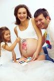 Glückliche schwangere Familie zeichnenden Bauches drei Lizenzfreies Stockbild