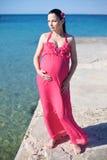 Glückliche schwangere Frau auf dem Strand Stockbilder