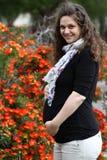Glückliche schwangere Frau in den Blumen erwartend Stockbilder