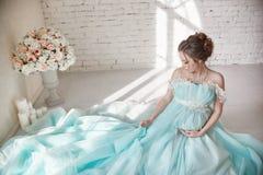 Glückliche schwangere Frau in den langen Abendkleiderrührenden Bauchhänden Aufwartung der Geburt eines Kindes, eine Frau in ihrem Stockbild