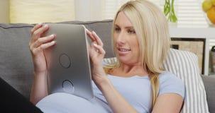 Glückliche schwangere Frau, die auf Couch unter Verwendung der Tablette liegt Stockfoto