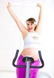 Glückliche schwangere Frau, die auf Fahrrad ausarbeitet Stockfoto