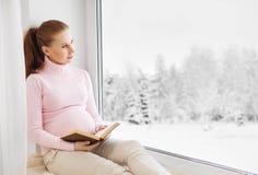 Glückliche schwangere Frau, die ein Buch beim Sitzen am Fenster liest Stockfotografie
