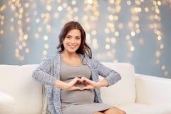 Glückliche schwangere Frau, die Herz zu Hause gestikulieren lässt Stockfotografie