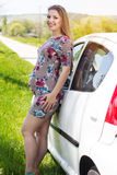 Glückliche schwangere Frau, die nahe weißem Auto steht Stockfotografie