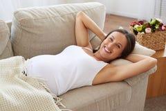 Glückliche schwangere Frau, die sich auf Sofa mit den Händen hinter ihr er hinlegt Stockfotografie