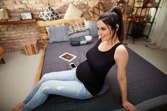 Glückliche schwangere Frau, die zu Hause auf Bett sitzt lizenzfreie stockfotos