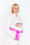 Glückliche schwangere Frau im Weiß mit rosa Band Lizenzfreies Stockfoto