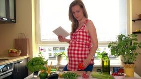Glückliche schwangere Frau mit dem Tabletten-PC-Computer, der zu Hause Gemüsesalat zubereitet stock video