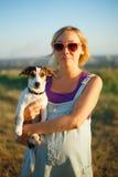 Glückliche schwangere Frau mit einem Hund bei Sonnenuntergang Stockfotos